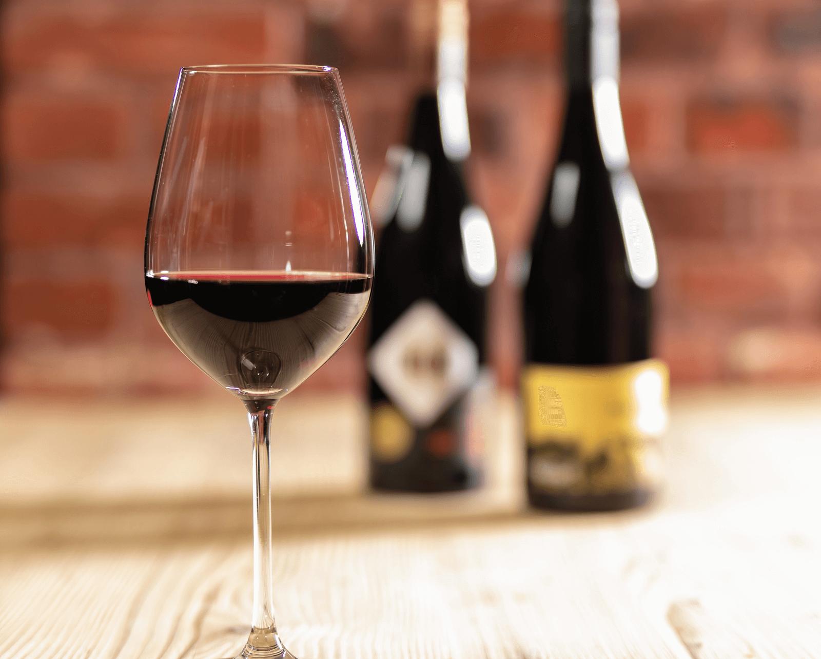 Rotweinglas mit Flaschen